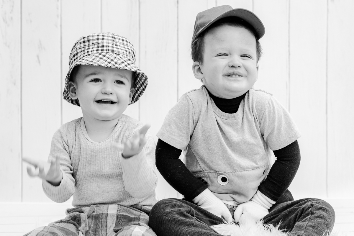 toddler brothers with hats on smiling at camera