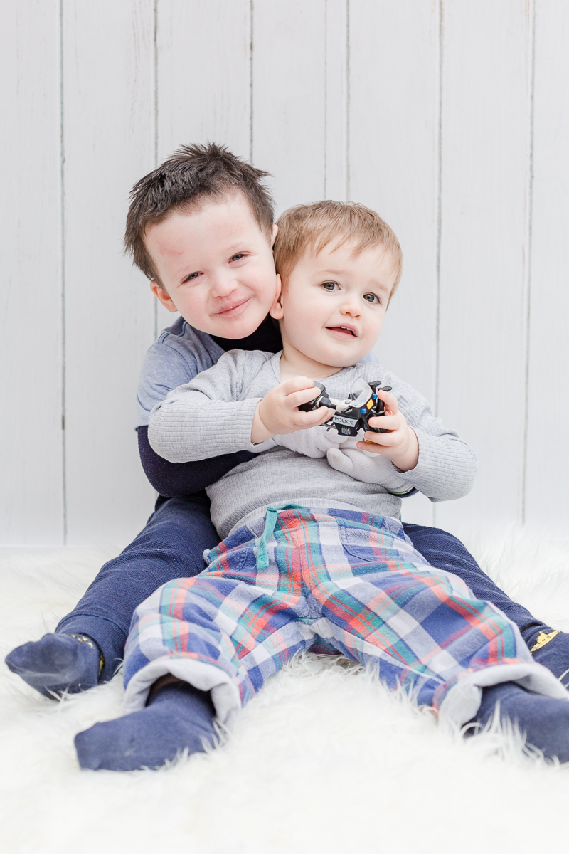 two boys in photo studio smiling at camera