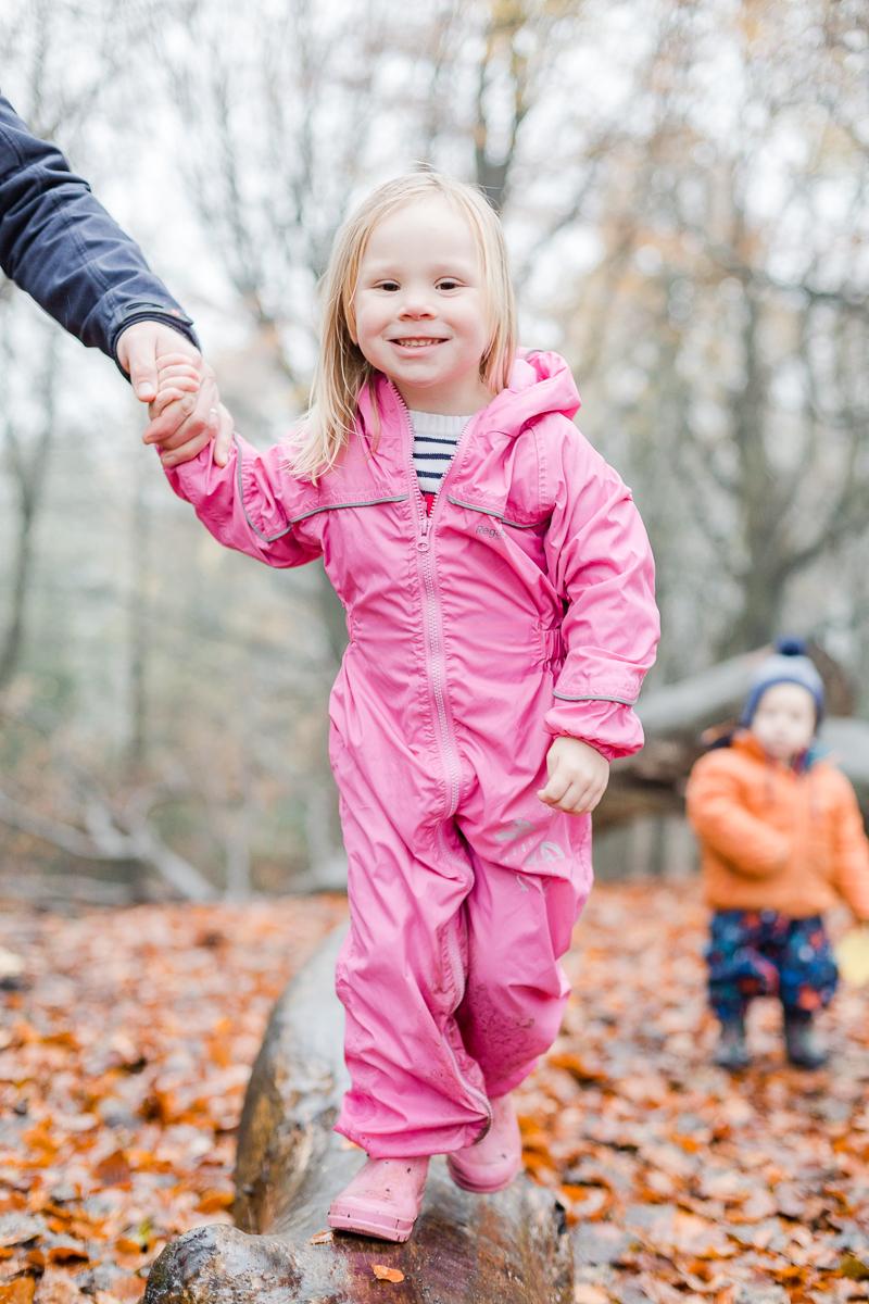 little girl walking along a autumn log