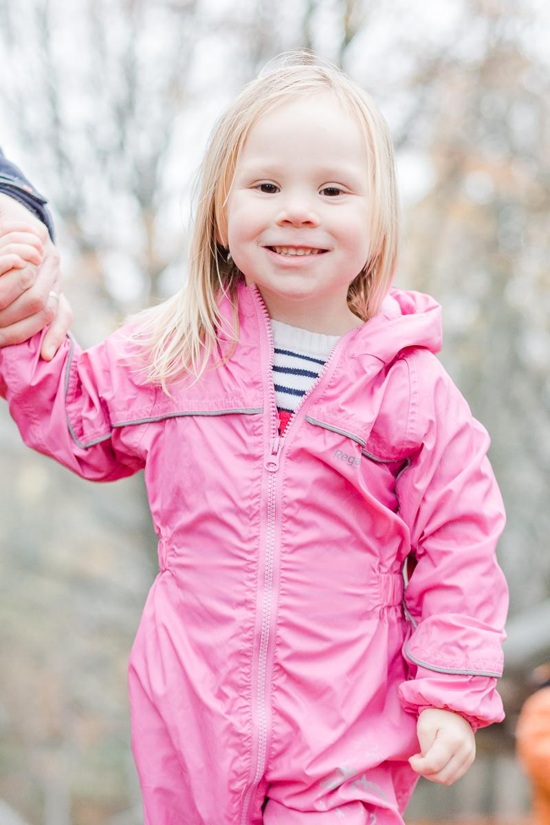 little girl in pink waterproofs in the woods