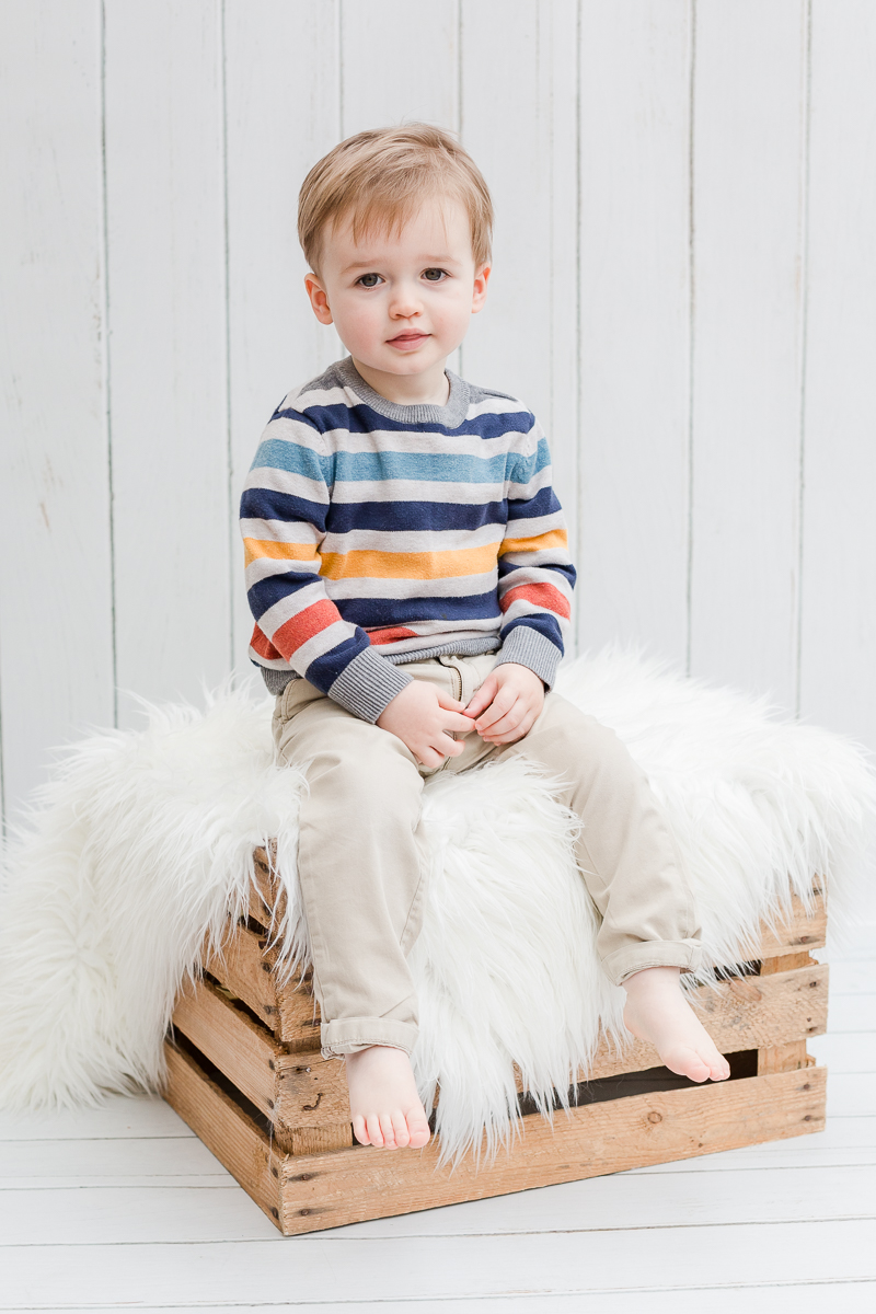 toddler in photo studio sat on a crate and fur in chinos and striped jumper