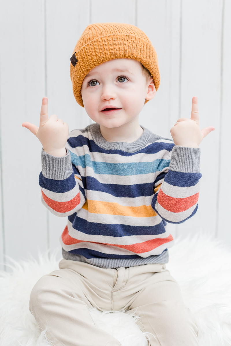 toddler with funny wool hat on pulling fun face