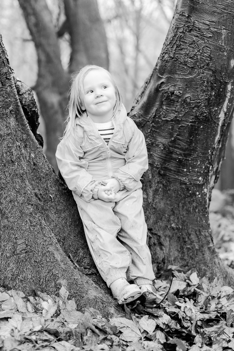 little girl leaning on a v shaped tree trunk with cheeky face