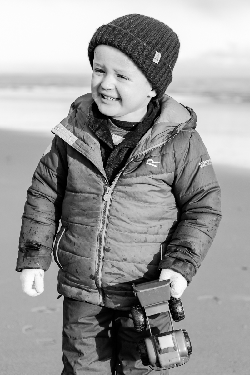little boy at the beech squinting and smiling