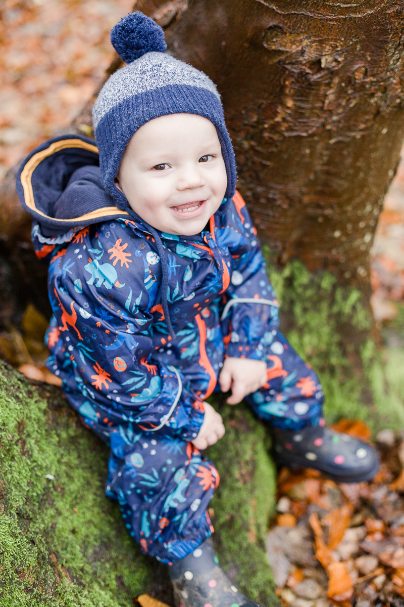toddler wrapped up in warm clothes sat on tree trunk cheeky smile