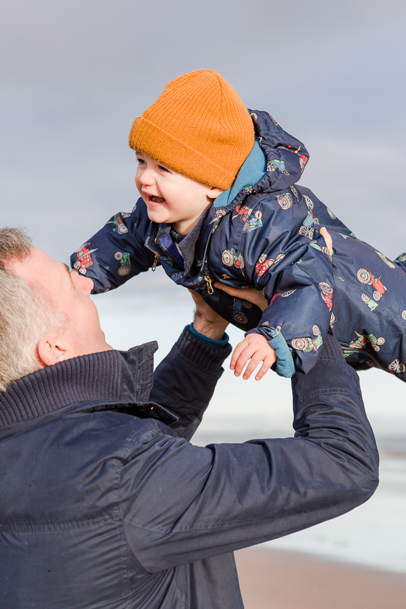 toddler being thrown into air by dad happy smiles
