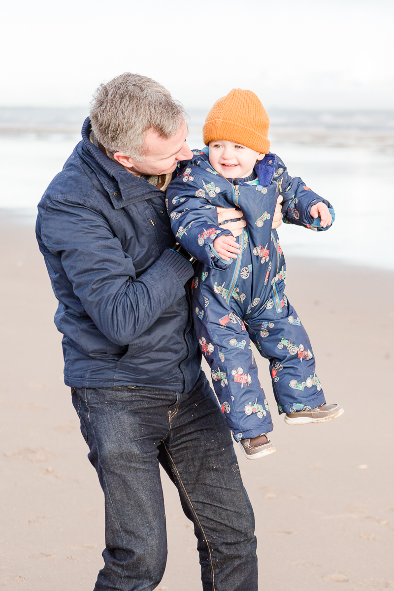 toddler smiling back at dad behind on beach