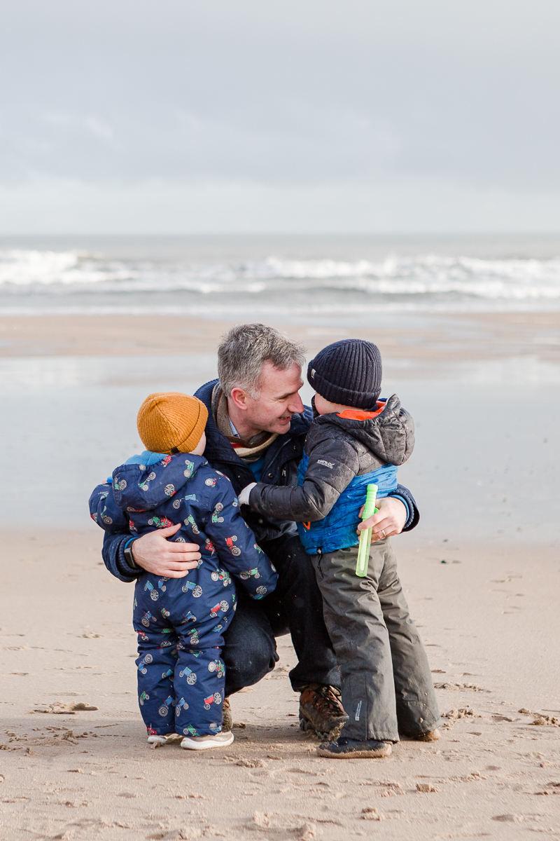 dad and two toddlers crouching down to talk on the beach