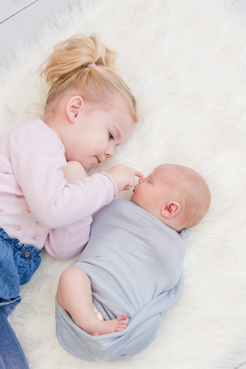 siblings lying on fur big sister touching babies nose side view