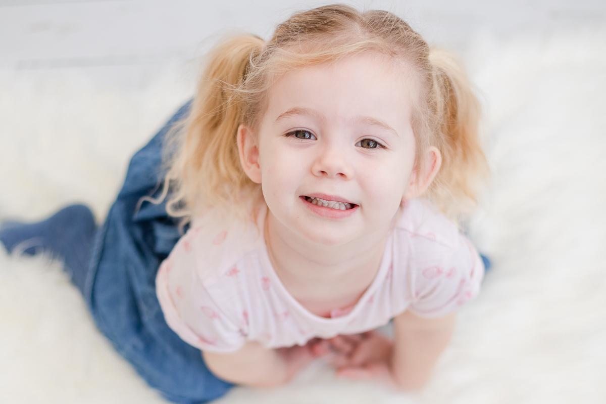 4 year old smiling up at camera