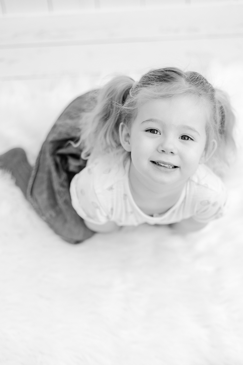 4 year old smiling up at camera black and white