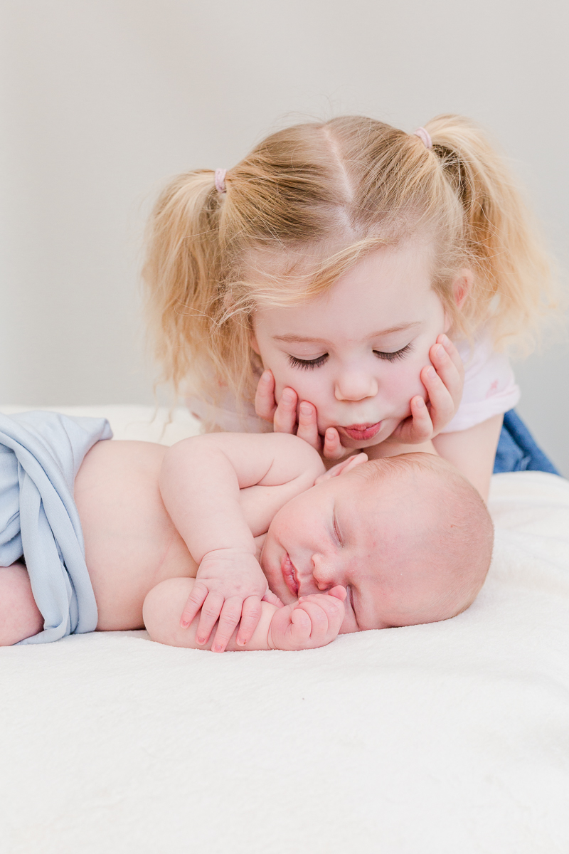 big sister leaning down to kiss baby boy