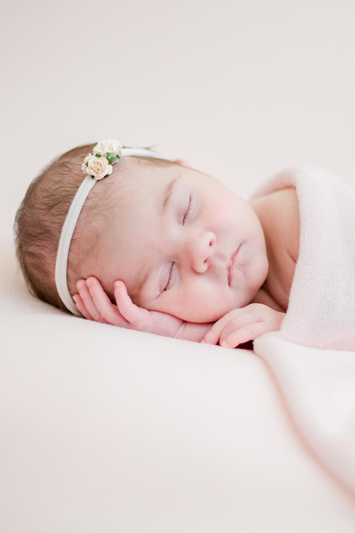 newborn baby girl asleep on her side head on hand under pink blanket