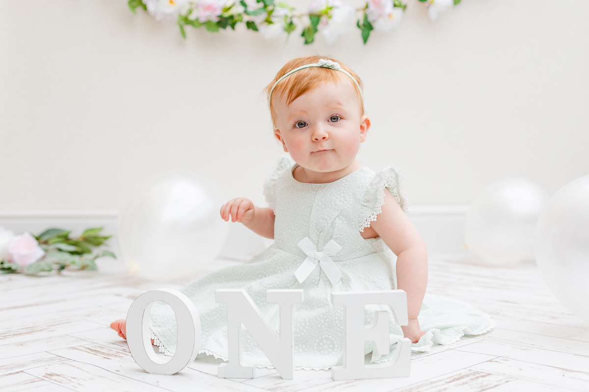 one year old baby in studio mint dress looking at camera
