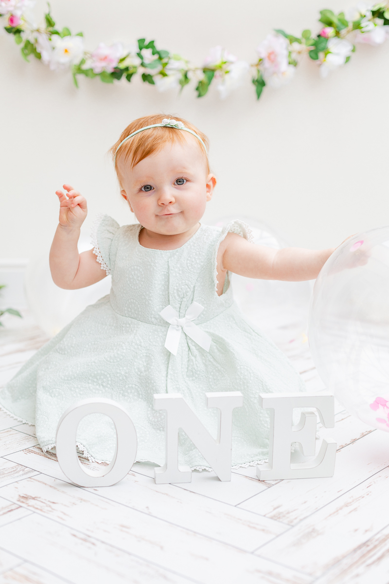 one year old girl I green mint dress with balloon in cake smash studio