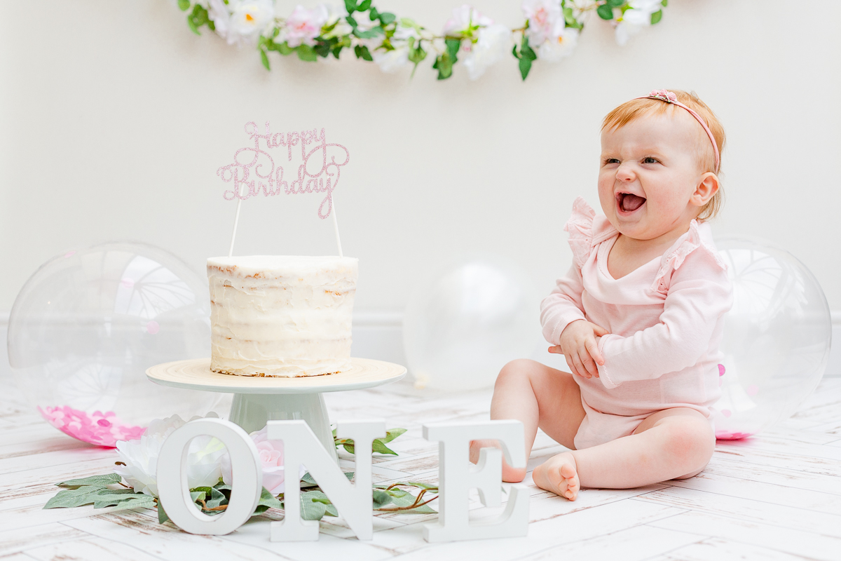 baby in cake smash photo studio exited to see cake