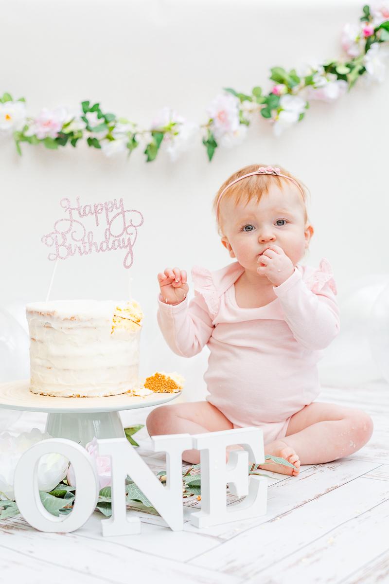 cake smash photo studio baby in pink eating cake