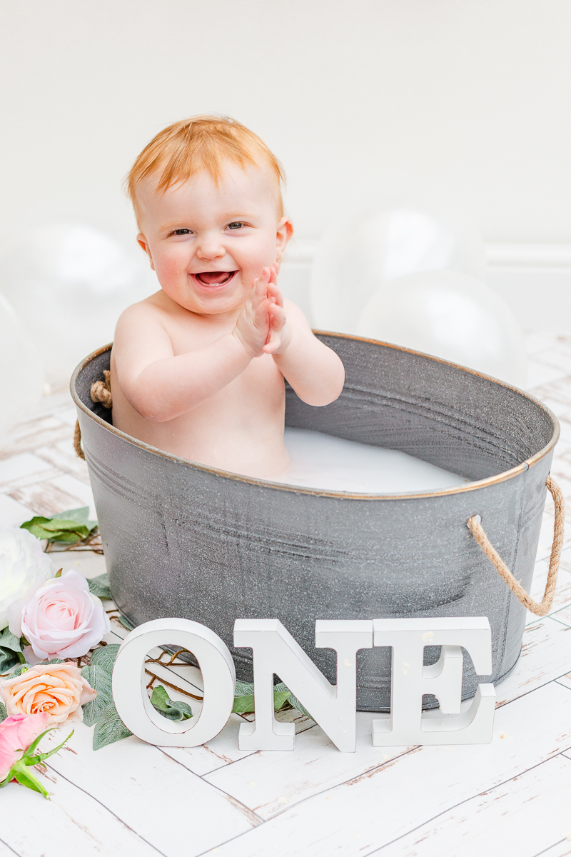 baby in metal bath tun clapping and smiling