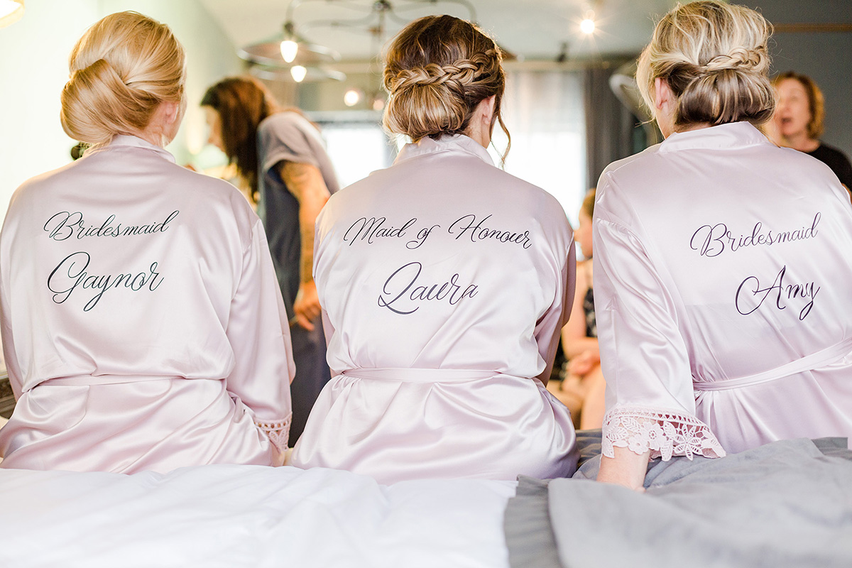 three bridesmaids sitting on bed with silk dressing gowns