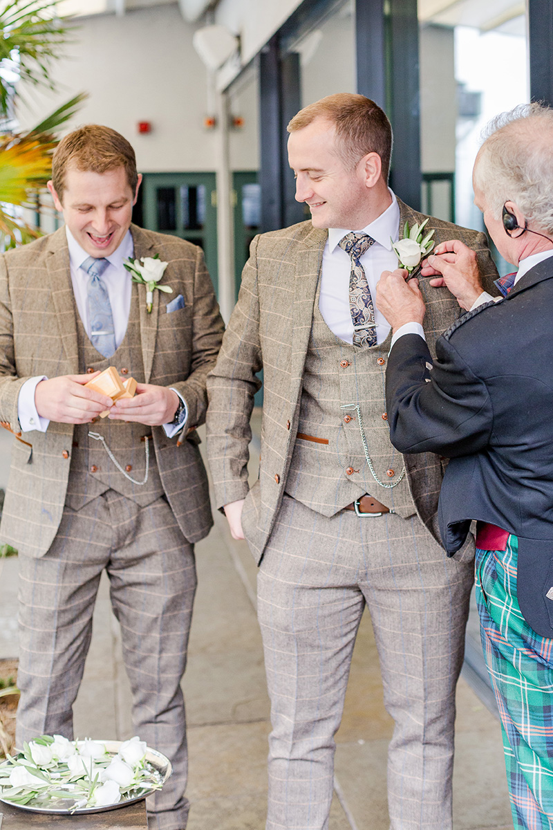 groom and best man having button holes attached