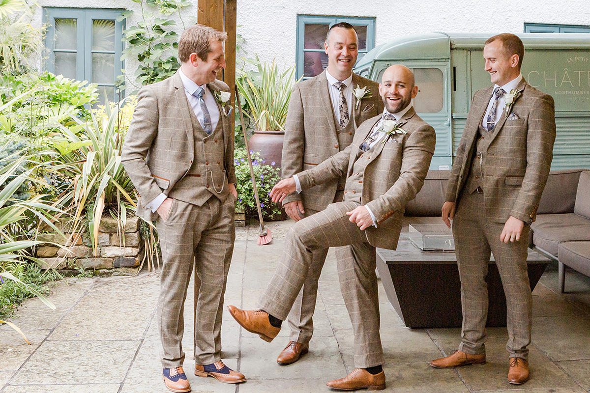 groomsmen joking around in gardens