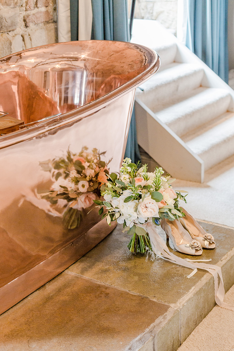 bouquet and wedding shoes next to shiny copper bath