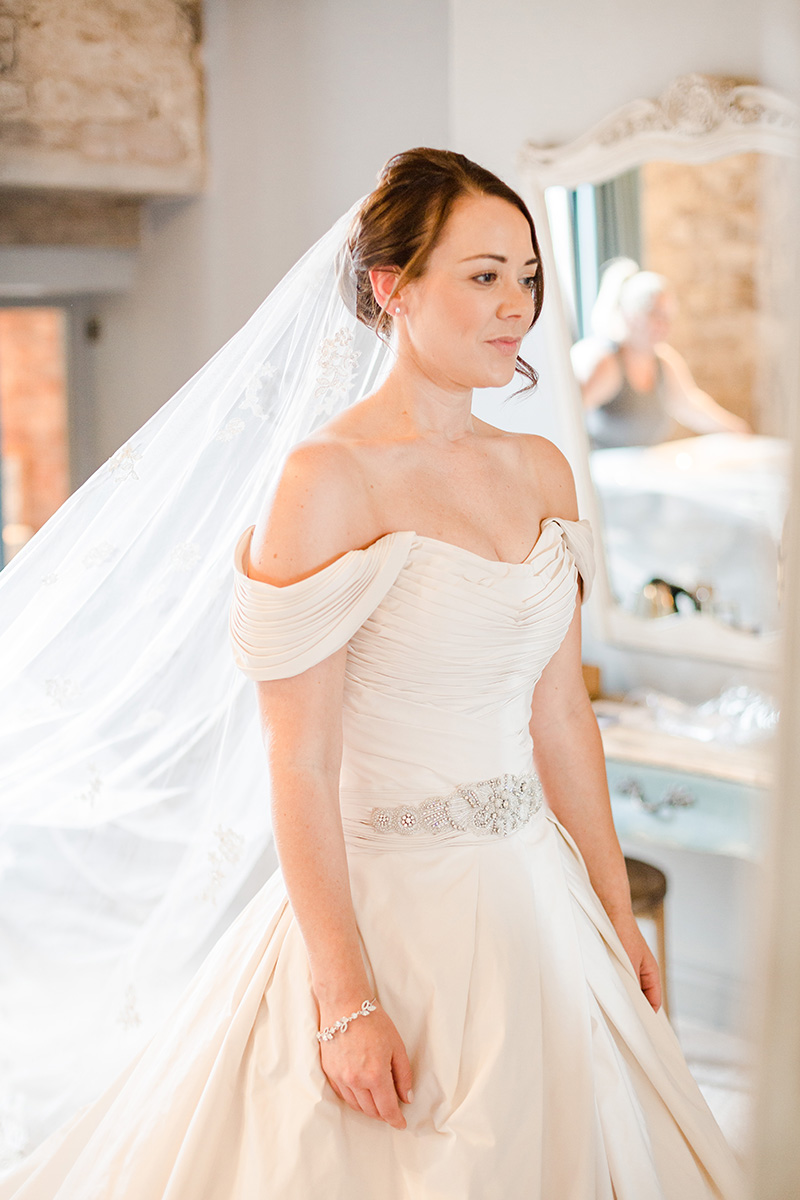 bride in gown and veil looking emotional in mirror