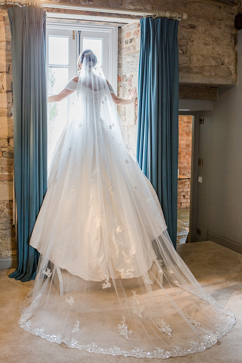 back of brides gown flowing down steps in window