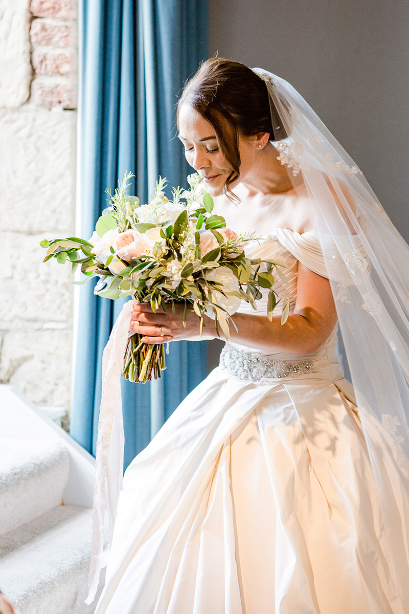bride stood in balcony window smelling bouquet
