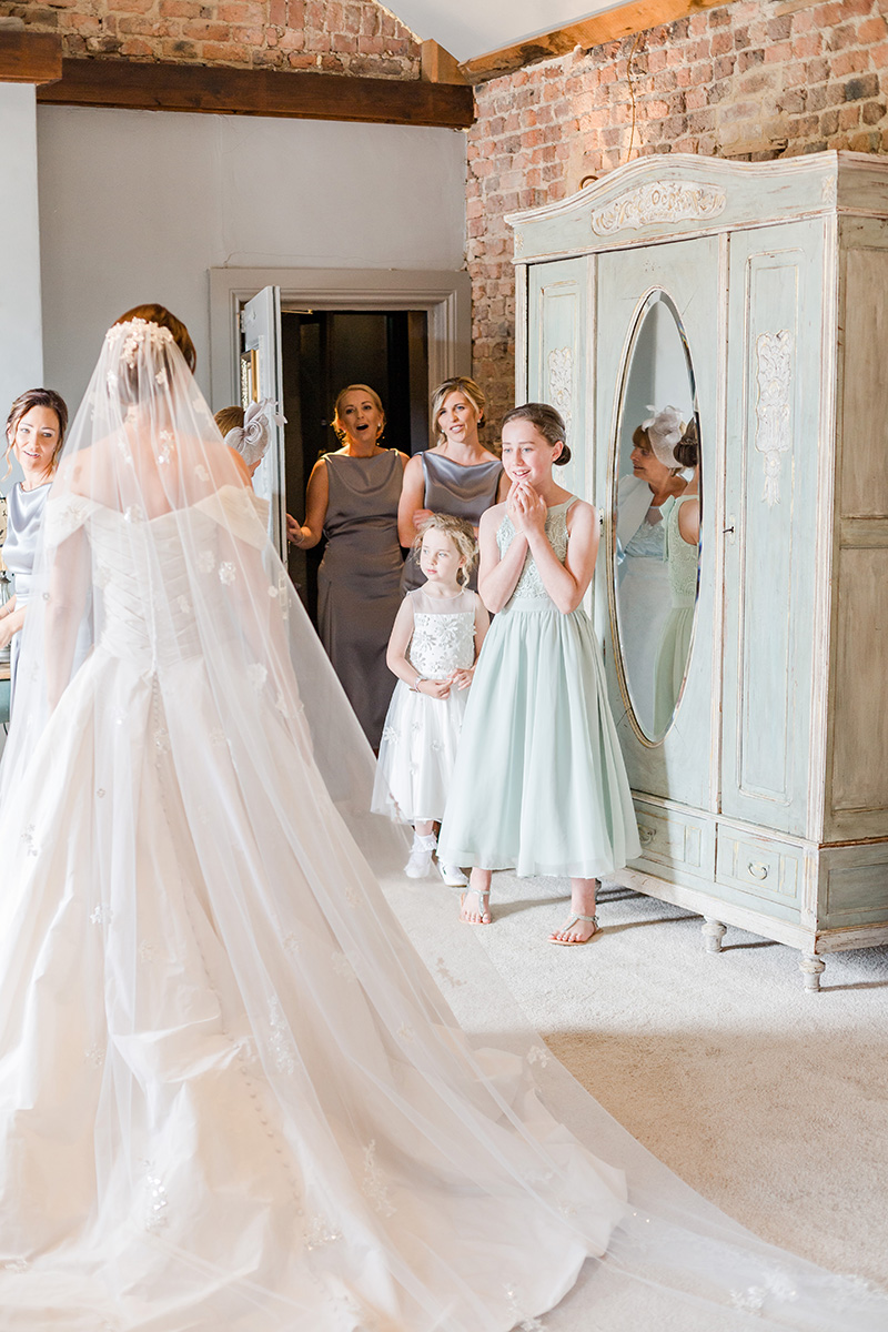 bridesmaids see bride for the first time in gown