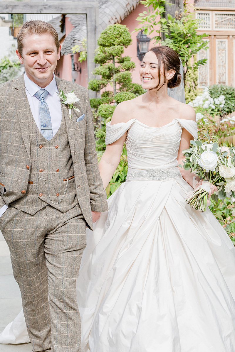 bride smiles at groom while walking through gardens