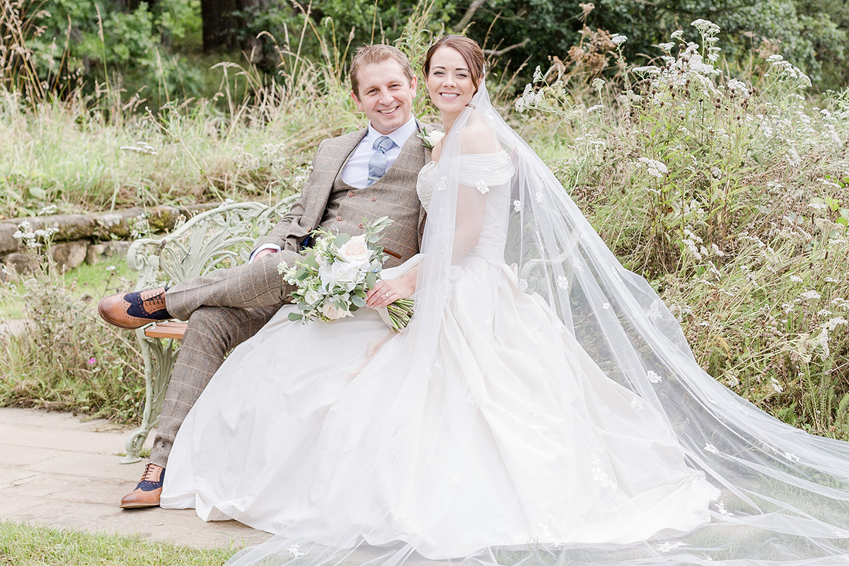 full length gown spilled out onto grass from bench with bride and groom