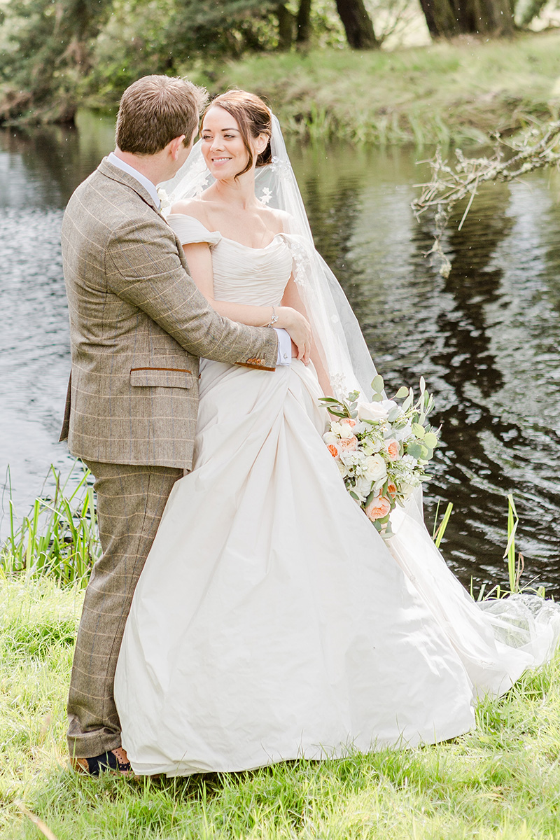 bride and groom infant of lake with arms around each other