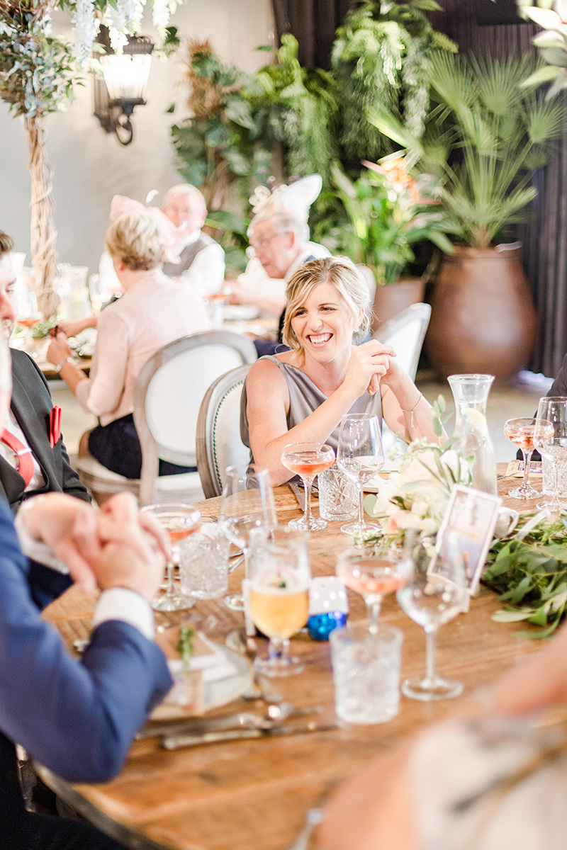 bridesmaid smiling at guests at at table
