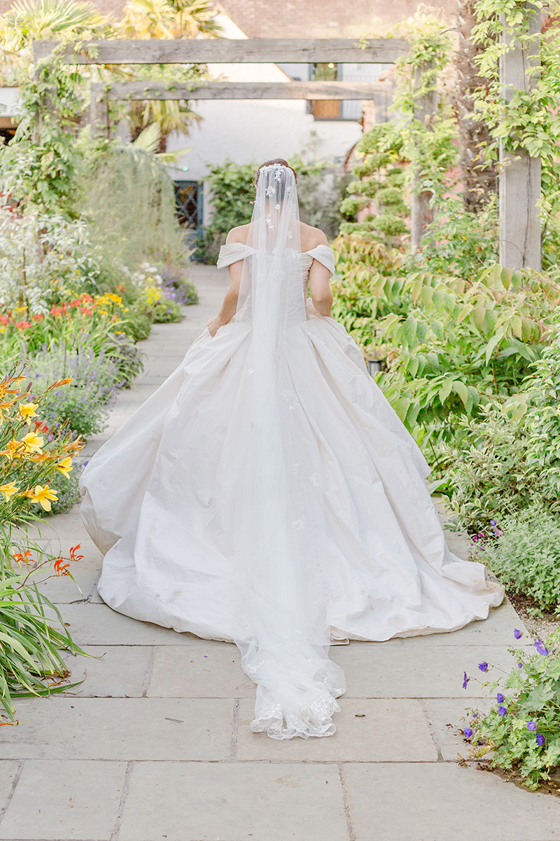 bride walking through garden archways