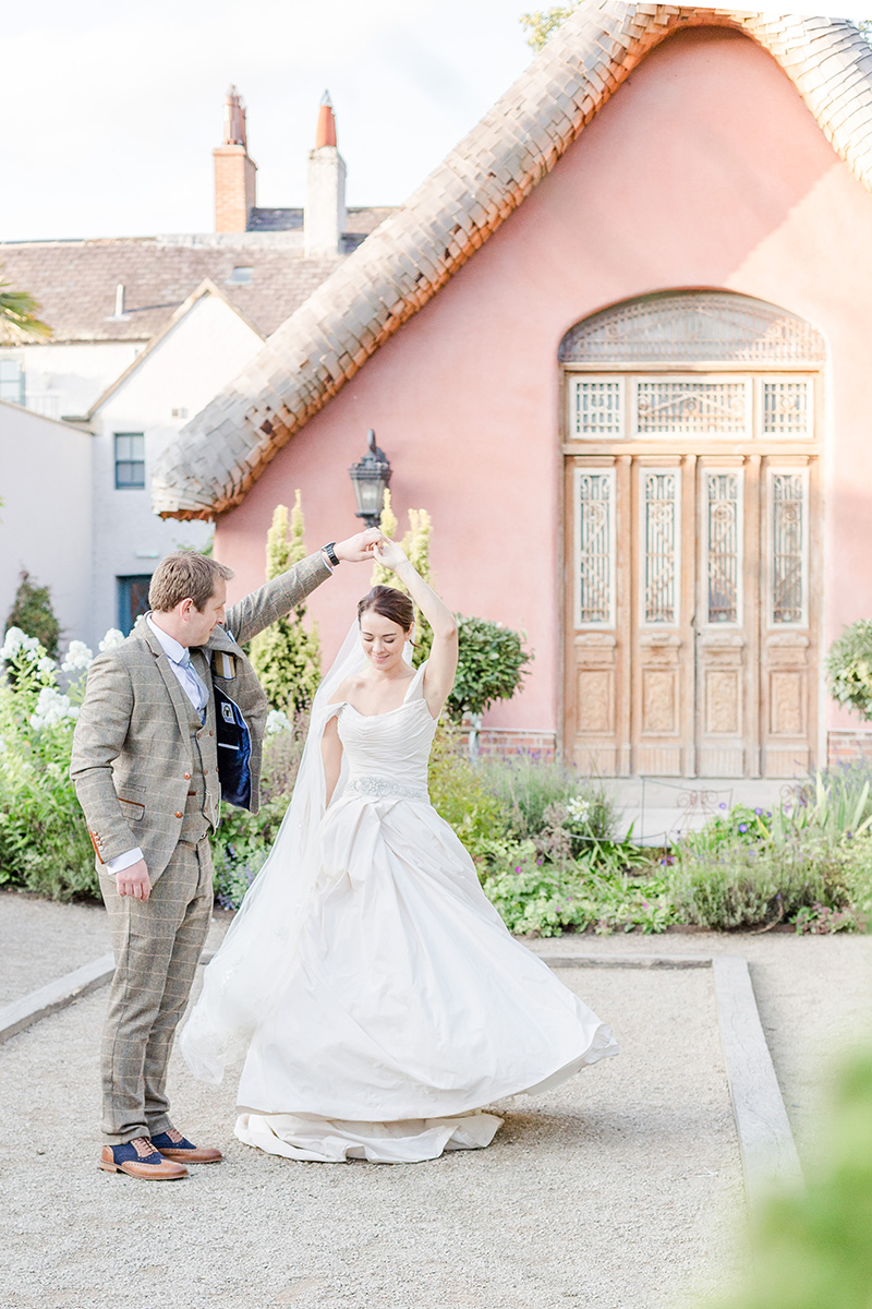 bride and groom dancing in front of pink house