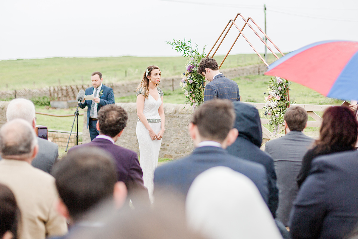bride and groom in field with copper wedding arch