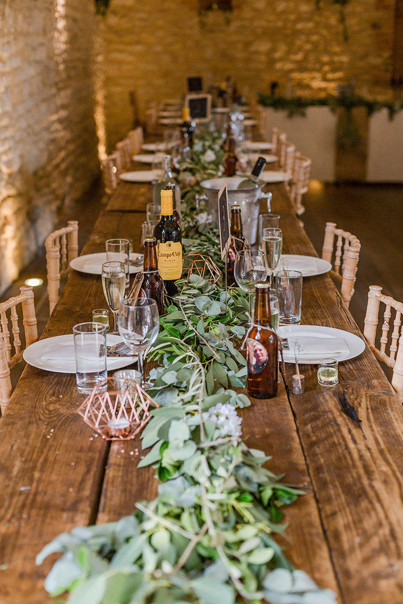 long wedding table set for meal with green foliage down the middle