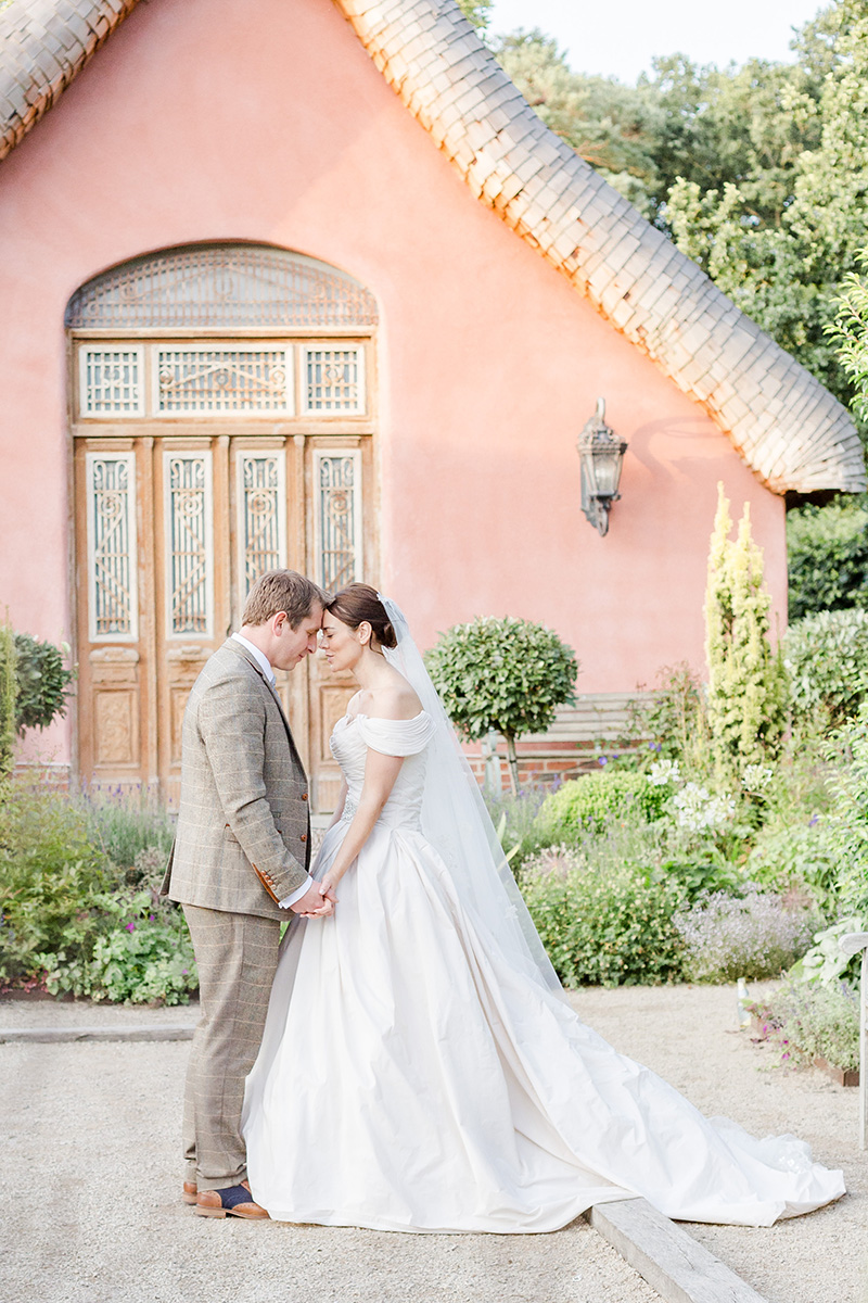 bide and groom forehead to forehead in gardens with pink house behind
