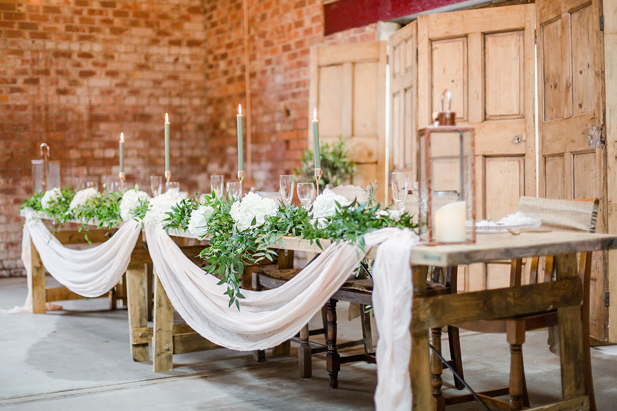 long tressel table with pink swags green foliage candles in front of wooden doors