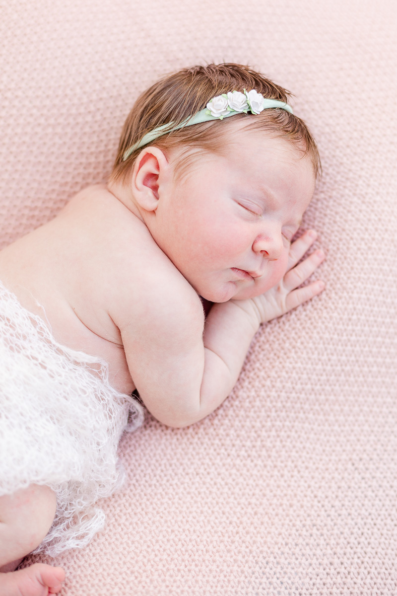 newborn baby girl asleep on pink blanket wrapped in lace blanket