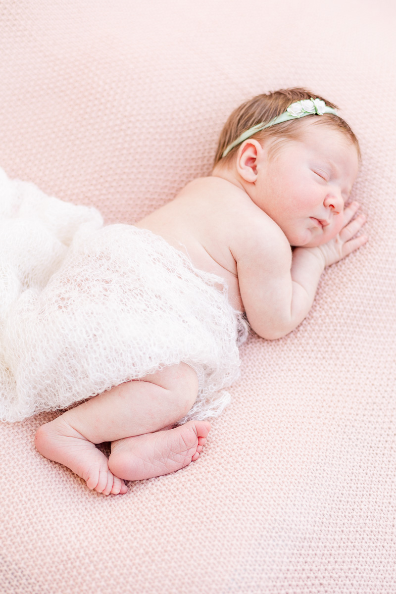 newborn baby asleep on her side on pink blanket wrapped in white lace