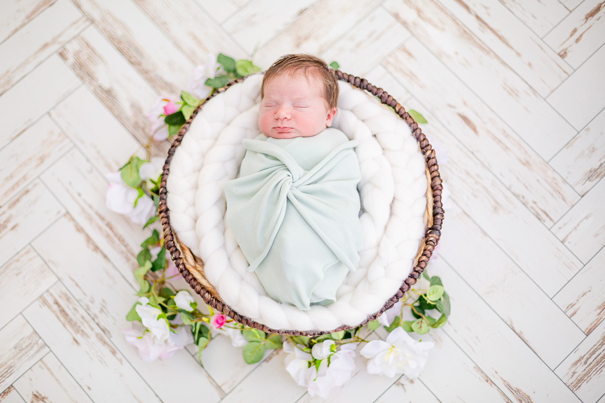newborn baby girl wrapped in mint green asleep in round basket with flower garland