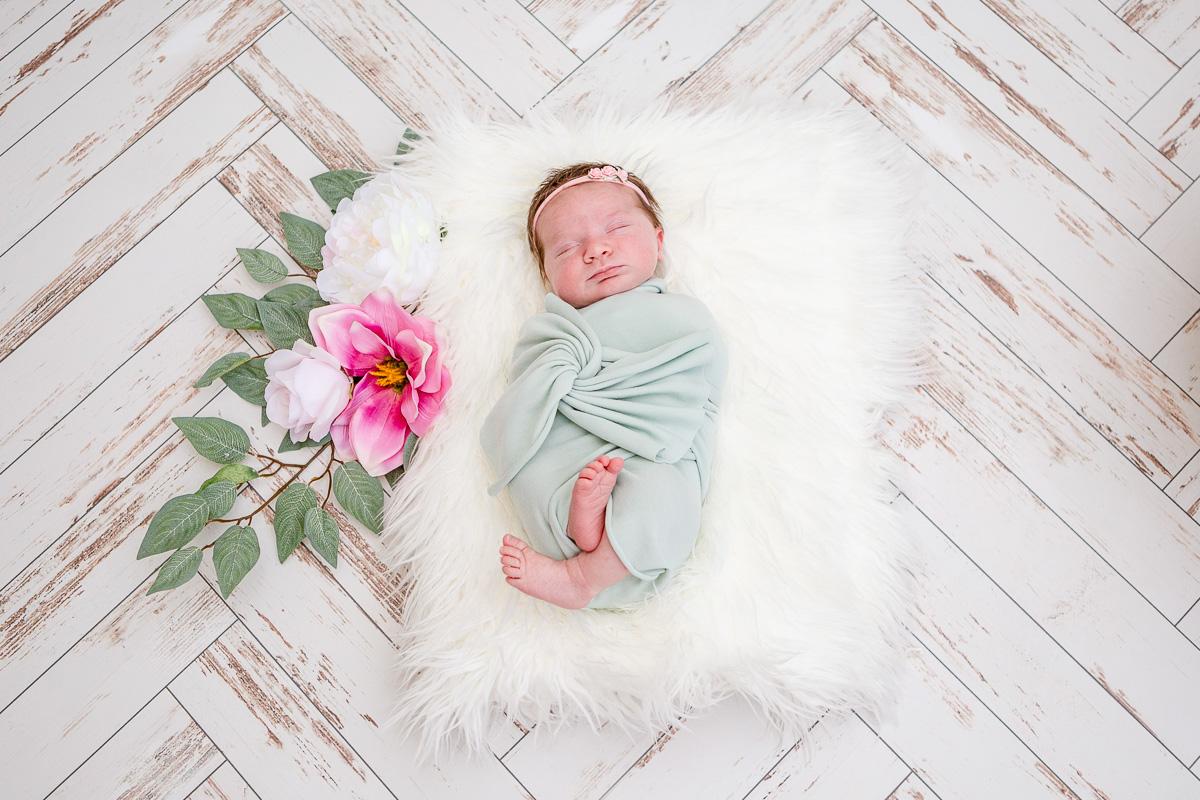 newborn baby girl asleep on white fur with flower garland