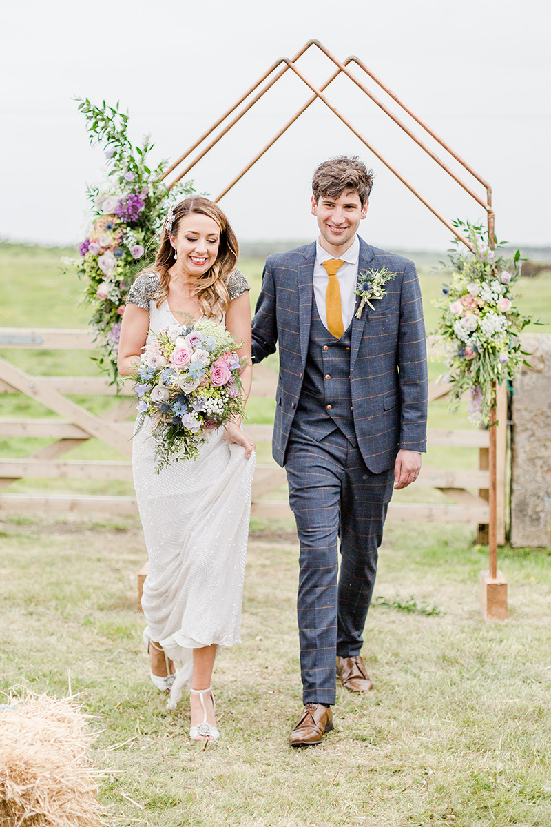 bride and groom in a field leaving alter with smiles