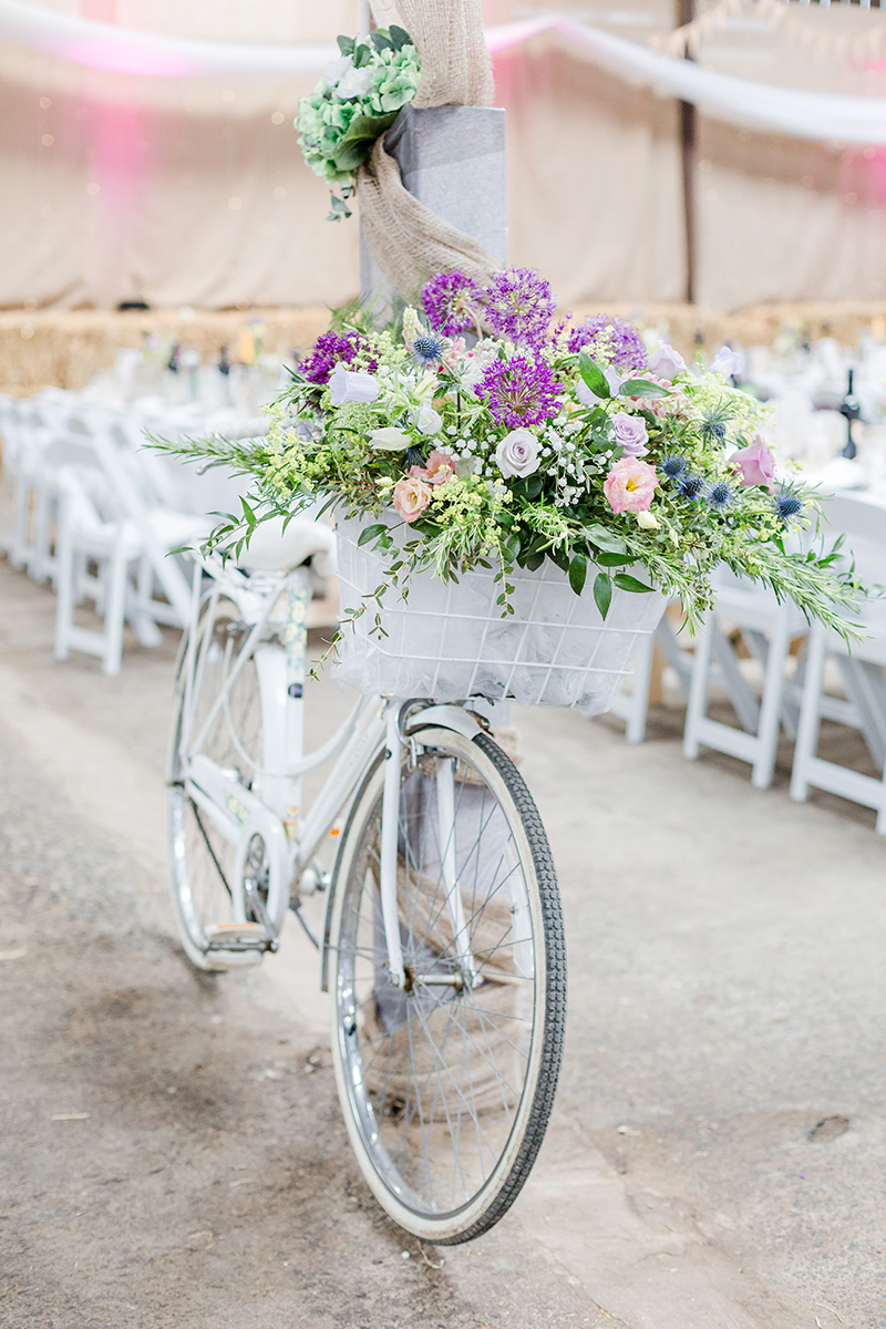 white vintage bicycle with large flour arrangment in basket