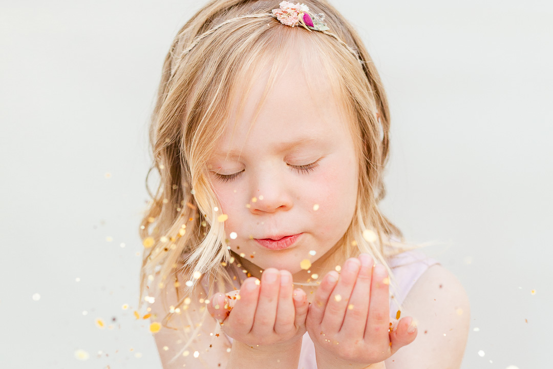 little girl blowing glitter