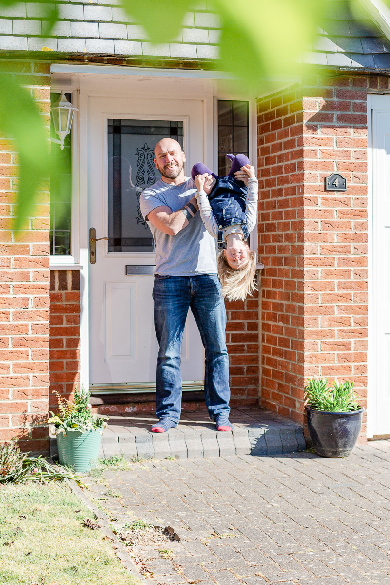 Daddy holding daughter upside down on doorstep