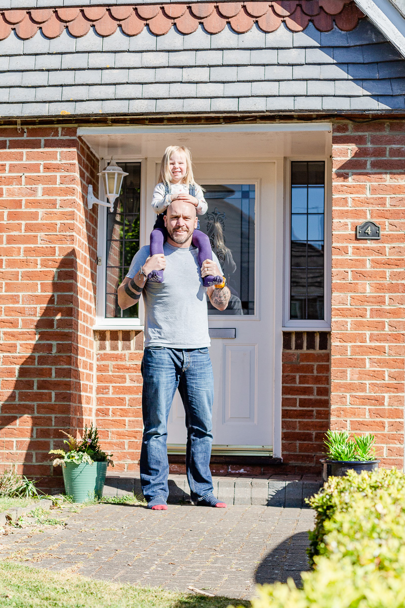 daddy holding daughter on shoulders on doorstep