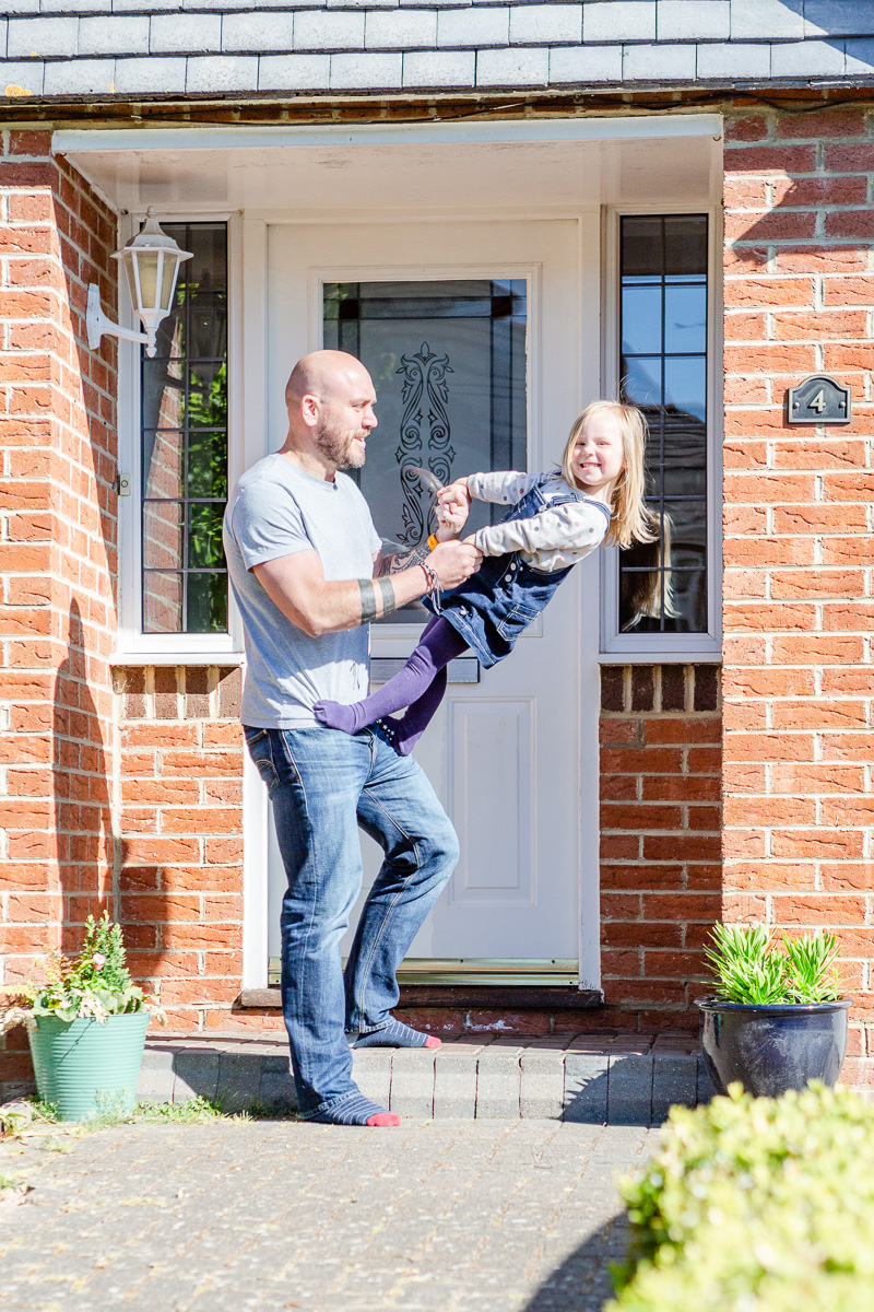 little girl and daddy playing on doorstep